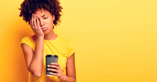 An exhausted young woman standing in front of a yellow background. She is wearing a yellow t-shirt, holding a large takeaway coffee in one hand, and resting her head in her other hand.