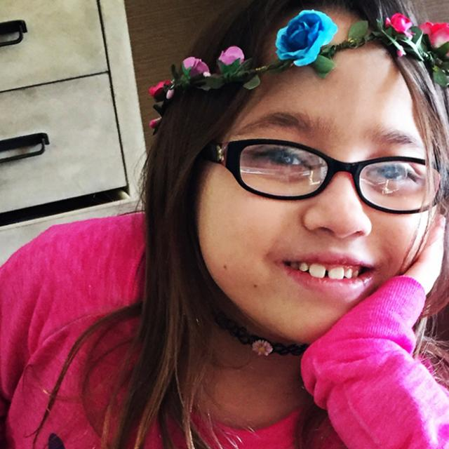 Image of a young girl who received a heart transplant. She is wearing a pink top and wearing a flower headband.