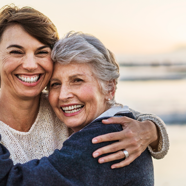 Portrait of happy daughter embracing senior woman on the beach
