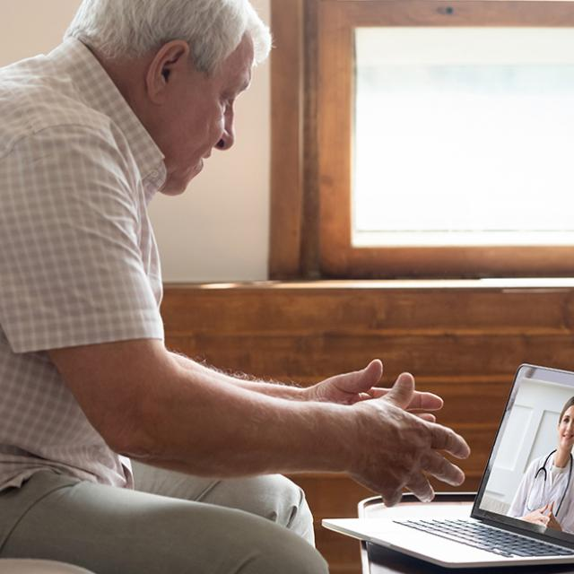 Elderly man using telehealth to see doctor through video chat at home during COVID-19 pandemic.