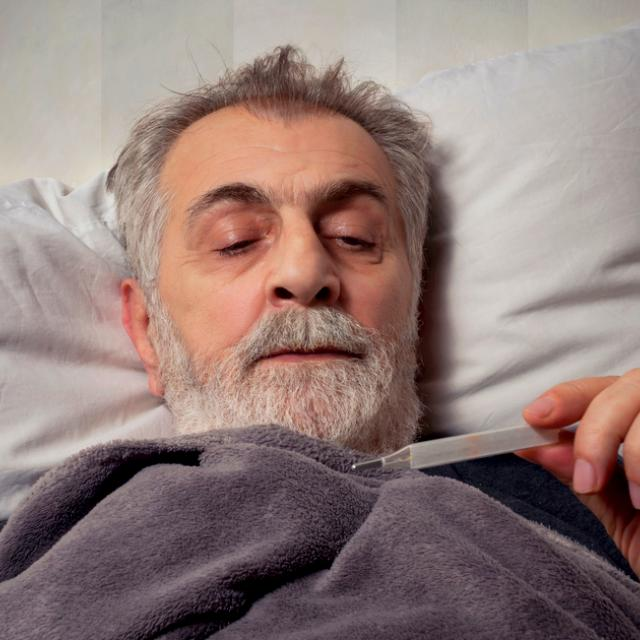 sick older man in bed holding a thermometer